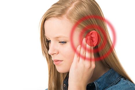 Woman holding sore ear